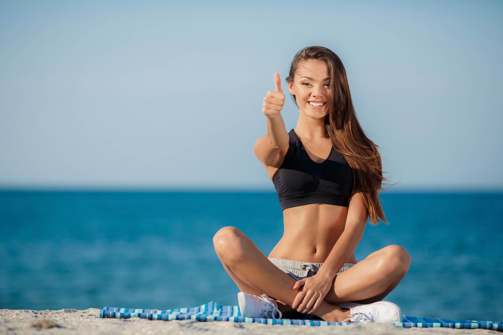Beautiful girl in lotus position on the beach
